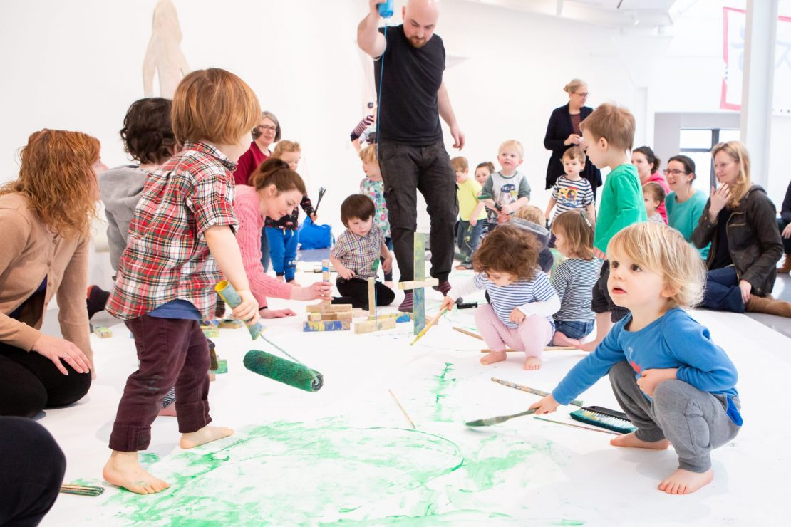 At the front of the image toddlers hold paint rollers and brushes, green paint is all over the floor. Behind them man is squeezing a bottle of blue paint onto the floor as other toddlers and their carers look on.