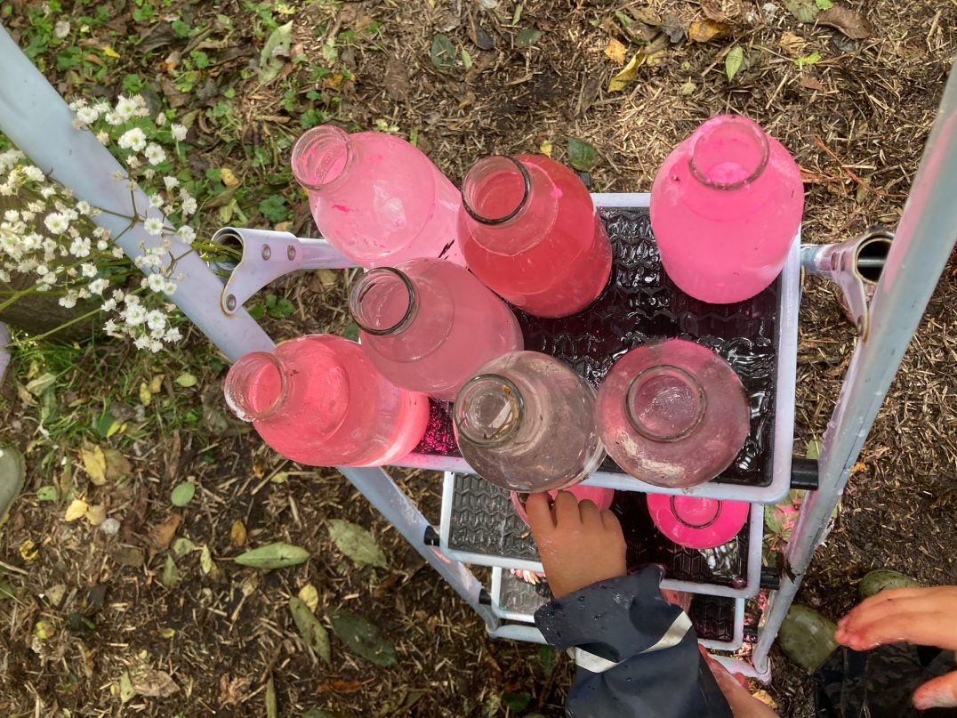 Glass milk bottles are filled with vivid pink liquids, the bottles are in a white milk crate on grass